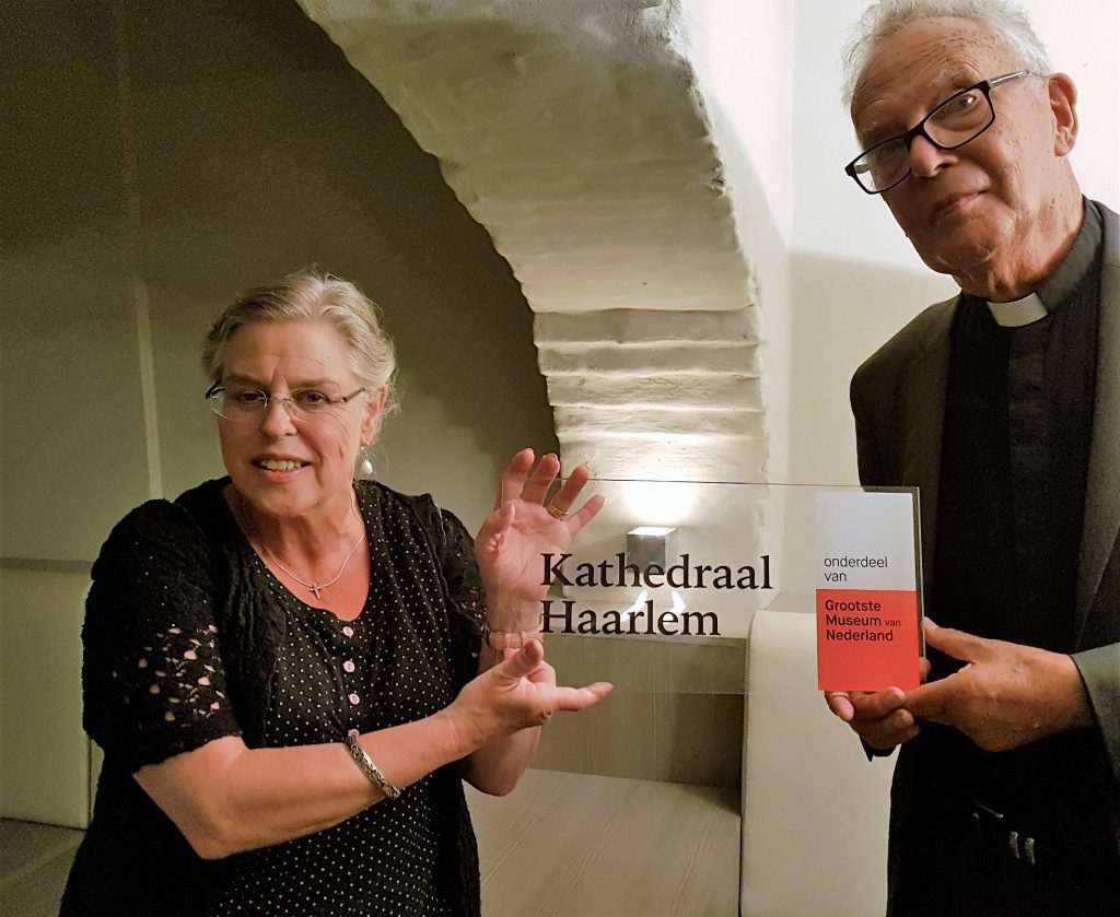 Kathedrale Basiliek sint Bavo is lid van het Grootste Museum van Nederland . Trots tonen kerkwacht Gerdi Gunst en pastoor H.van Ogtrop het bordje.
